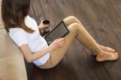 La muchacha se está sentando en el piso con una tableta en sus manos que lee las noticias, una taza de controles del café en mano imagenes de archivo