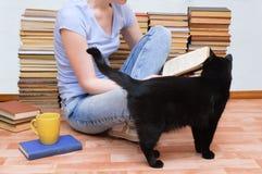 la muchacha se está sentando en el piso con una taza de té y está leyendo un libro al lado de un gato negro imágenes de archivo libres de regalías