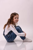 La muchacha se está sentando en el suelo Foto de archivo