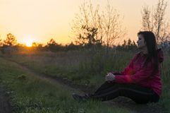 La muchacha se está sentando en la hierba Fotos de archivo