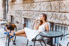 La muchacha se está sentando en la calle con café y una bicicleta Imágenes de archivo libres de regalías