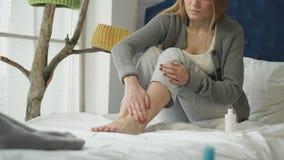 La muchacha se está sentando en la crema de las frotaciones de la cama en su pierna almacen de video