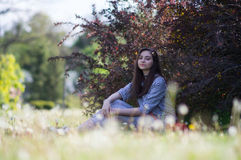 La muchacha se está sentando en la hierba en el parque Imagen de archivo