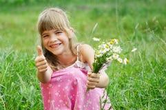 La muchacha se está sentando en la hierba y la sonrisa Fotografía de archivo libre de regalías