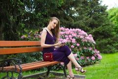 La muchacha se está sentando en un banco Fotos de archivo libres de regalías