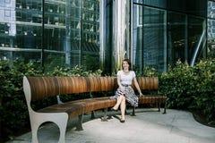 La muchacha se está sentando en un banco Imagen de archivo