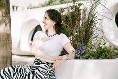 La muchacha se está sentando en un banco Foto de archivo libre de regalías