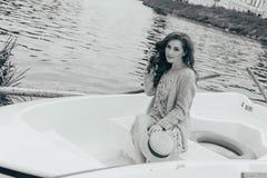 la muchacha se está sentando en un barco blanco en el río en manos sostiene un sombrero del sol Foto blanco y negro de Pekín, Chi imagenes de archivo