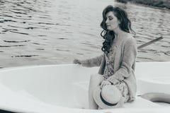 la muchacha se está sentando en un barco blanco en el río en manos sostiene un sombrero del sol Foto blanco y negro de Pekín, Chi foto de archivo libre de regalías