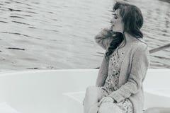 la muchacha se está sentando en un barco blanco en el río en manos sostiene un sombrero del sol Foto blanco y negro de Pekín, Chi foto de archivo