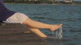 La muchacha se está sentando en un embarcadero de madera y está salpicando con sus pies en el agua almacen de video