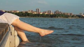 La muchacha se está sentando en un embarcadero de madera y está salpicando con sus pies en el agua metrajes