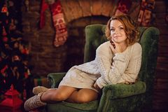 la muchacha se está sentando en una silla cerca de la chimenea Fotografía de archivo libre de regalías
