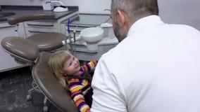 La muchacha se está sentando en una silla del dentista y está mostrando los dientes almacen de video