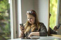 La muchacha se está sentando en una tabla que mecanografía en un smartphone Fotografía de archivo