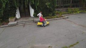 La muchacha se está sentando en una vespa cerca de la casa del parque Tirado en abejón almacen de video