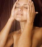 La muchacha se lava la cara con los ojos cerrados Imagen de archivo libre de regalías