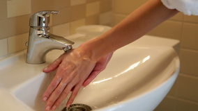 La muchacha se lava las manos debajo del golpecito almacen de metraje de vídeo