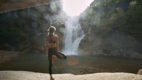 La muchacha se opone en la posición de la yoga a los rayos de Sun del río