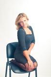 La muchacha se pone en cuclillas en una silla Fotografía de archivo libre de regalías