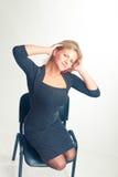La muchacha se pone en cuclillas en una silla Foto de archivo libre de regalías