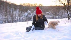 La muchacha se ríe con los snowflackes y su animal doméstico metrajes