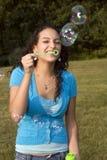 La muchacha se ríe de burbujas que soplan Foto de archivo