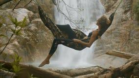 La muchacha se relaja en hamaca en la cascada brillante cercana