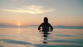 La muchacha se relaja en la piscina en la puesta del sol metrajes
