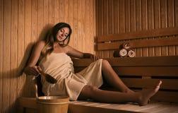 La muchacha se relaja en una sauna y juegos con agua imagenes de archivo