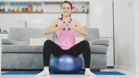 La muchacha se sentó en la bola que hacía diversos ejercicios de los deportes