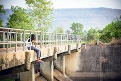 La muchacha se sentaba en el puente en el bosque Foto de archivo