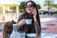La muchacha se sienta al aire libre en un café y negociaciones a su teléfono móvil imágenes de archivo libres de regalías