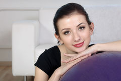 La muchacha se sienta cerca de una bola gimnástica Foto de archivo