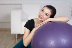 La muchacha se sienta cerca de una bola gimnástica Fotografía de archivo