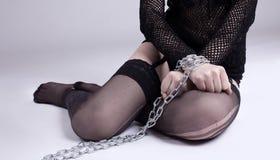 La muchacha se sienta con el encadenamiento en las manos - juegos del bdsm Imágenes de archivo libres de regalías