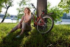 La muchacha se sienta con una bicicleta Imagen de archivo libre de regalías