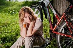 La muchacha se sienta con una bicicleta Foto de archivo libre de regalías