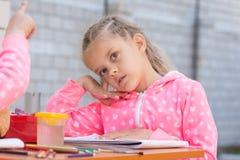 La muchacha se sienta cuidadosamente en la tabla con los accesorios para pintar Imagen de archivo libre de regalías