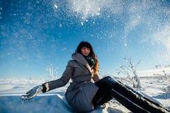 La muchacha se sienta debajo de nieve que cae Fotos de archivo libres de regalías