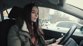La muchacha se sienta detrás de la rueda de su coche almacen de metraje de vídeo