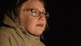 La muchacha se sienta el fuego en la noche y mirándolo Vista grande de su cara del lado almacen de video