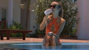 La muchacha se sienta en agua de las bebidas de la piscina que disfruta de ocio