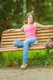 La muchacha se sienta en banco Fotos de archivo libres de regalías