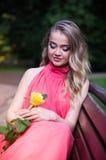 La muchacha se sienta en banco de parque Foto de archivo libre de regalías