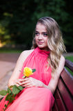 La muchacha se sienta en banco de parque Imagen de archivo libre de regalías