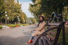 La muchacha se sienta en banco en capa y zapatos rojos imágenes de archivo libres de regalías
