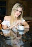 La muchacha se sienta en café Imagen de archivo