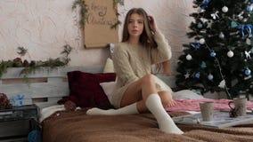 La muchacha se sienta en la cama al lado del árbol de navidad La atmósfera del Año Nuevo metrajes
