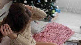 La muchacha se sienta en la cama al lado del árbol de navidad Atmósfera del ` s del Año Nuevo metrajes